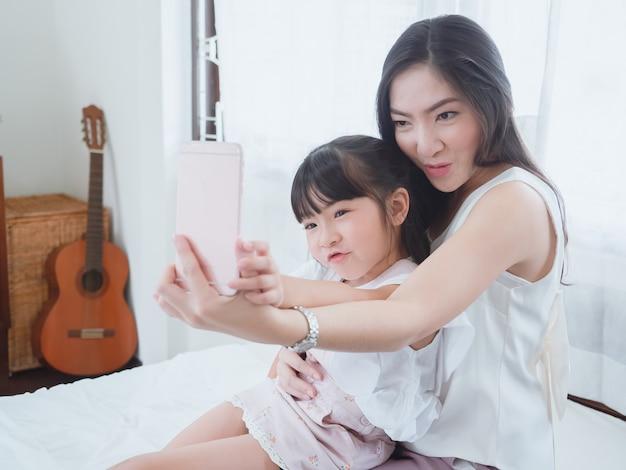 A criança está brincando na cama com a mãe dela