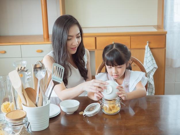 A criança está brincando na cozinha com a mãe dela