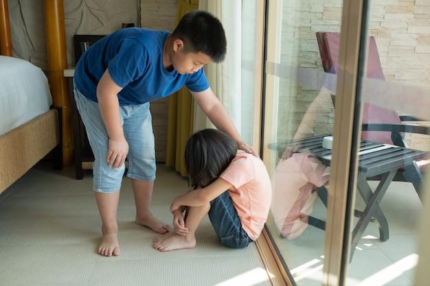 A criança está chorando, criança infeliz sentada no chão