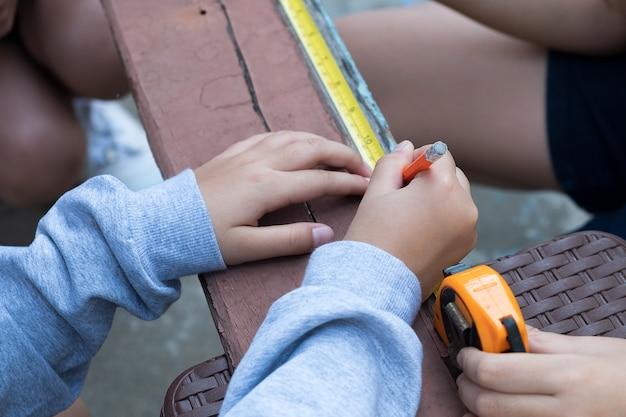A criança está consertando madeira com lápis e fita métrica
