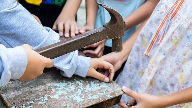 A criança está consertando madeira com pregos e martelo