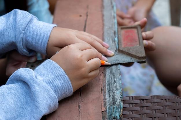 A criança está consertando madeira com um lápis e uma cena