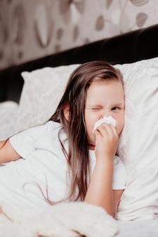 A criança está deitada com o nariz inchado e vermelho devido a coriza, um resfriado e uma segunda onda do vírus.
