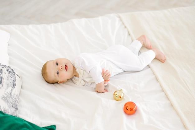 A criança está deitada na cama do quarto rodeada de bolas de brinquedos da árvore de natal e rindo