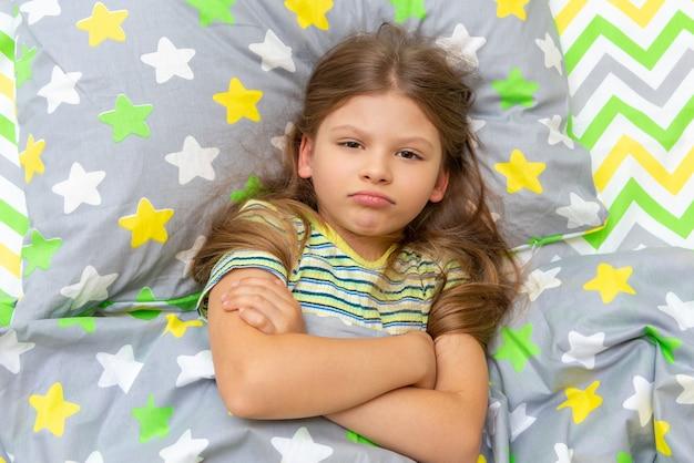 A criança está deitada na cama e fica indignada, não quer se levantar para ir estudar.