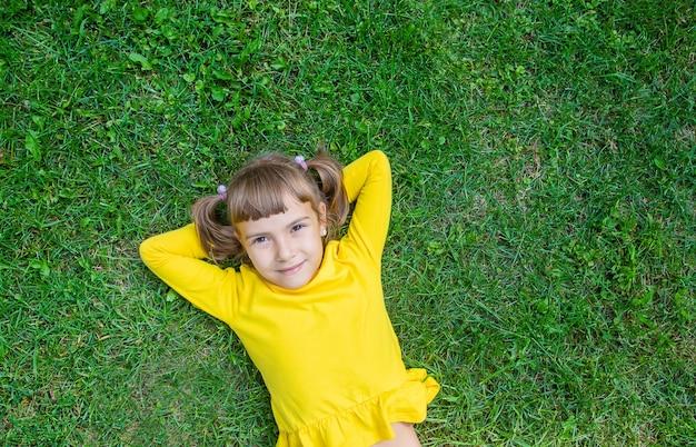 A criança está deitada na grama.