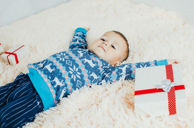 A criança está deitada no cobertor fofinho de lã, ao lado dele um monte de presentes, a criança está muito feliz