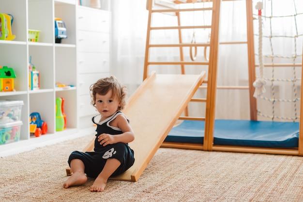 A criança está envolvida no complexo esportivo de madeira das crianças em casa.