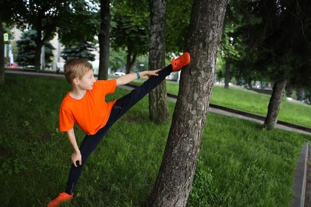 A criança está no parque fazendo alongamento, o menino está fazendo exercícios de ioga