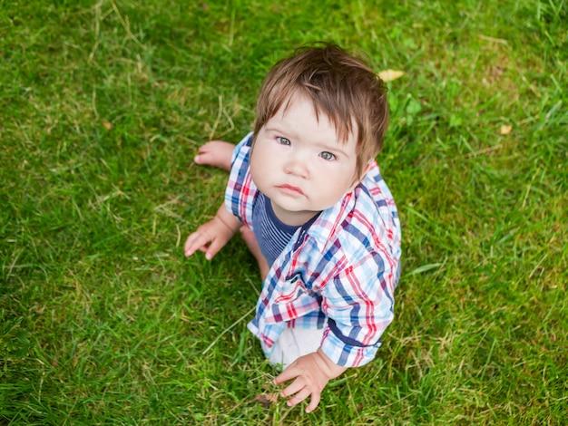 A criança está olhando para cima. no fundo da grama verde