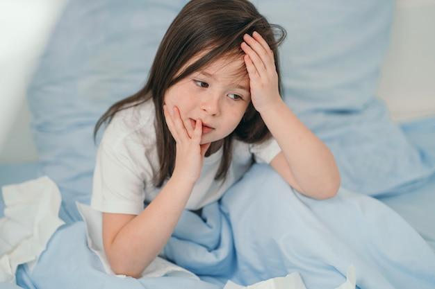 A criança está resfriada e está sendo tratada em casa. a garota está com dor de cabeça. a criança está doente e deita na cama