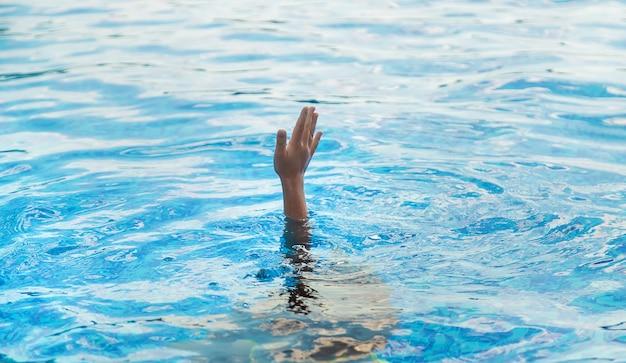 A criança está se afogando na água. foco seletivo. miúdo. Foto Premium