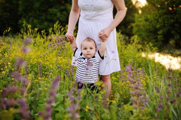 A criança está segurando a mão da mãe na superfície de flores silvestres. primeiros passos do bebê