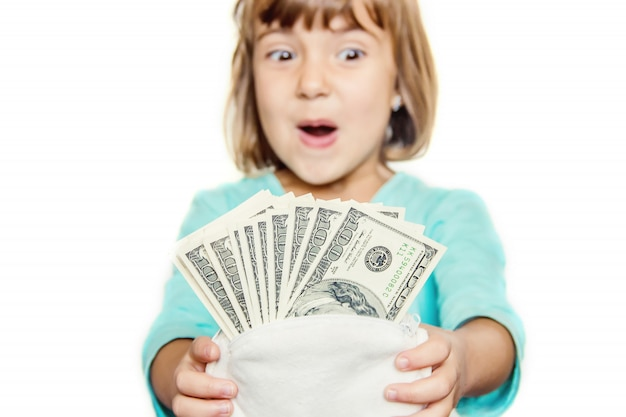 A criança está segurando dinheiro em suas mãos. foco seletivo.