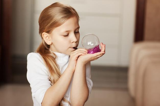A criança está segurando um brinquedo chamado muco, a criança está se divertindo e experimentando.