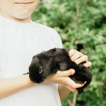A criança está segurando um coelhinho preto nas mãos da vegetação.