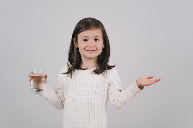 A criança está segurando um copo d'água. a menina quer beber água.
