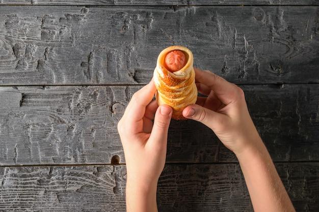 A criança está segurando uma salsicha fresca caseira na massa sobre uma mesa de madeira preta. a vista do topo.