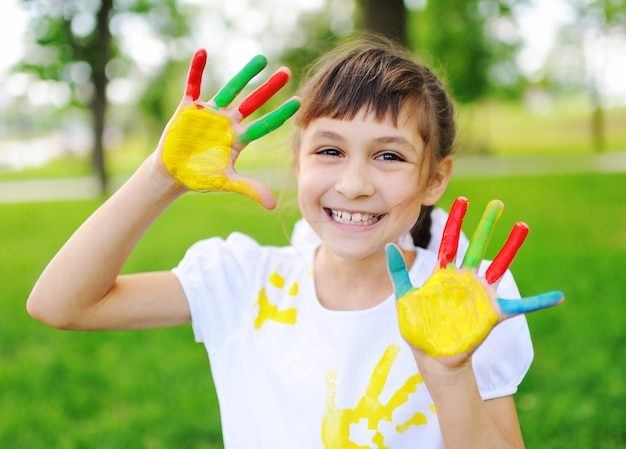 A criança está suja com roupas de cores brilhantes, pintadas a dedo, sorrindo no parque.