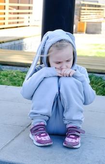 A criança está triste na rua. a criança está sozinha.