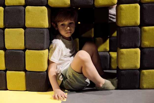 A criança estava triste no centro de recreação infantil entre blocos cúbicos macios. brinquedos infantis. organização do parque infantil. problemas infantis. autismo. centros educacionais e educacionais para crianças.
