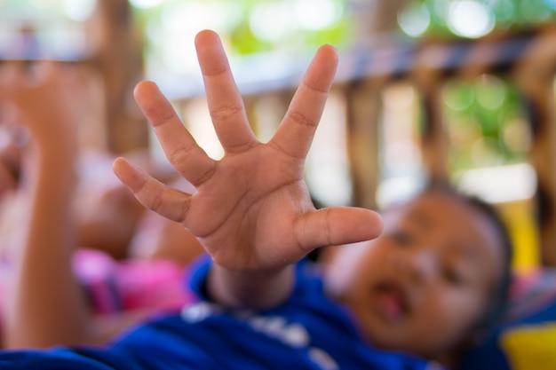 A criança estende a mão para a câmera