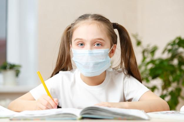 A criança estuda em casa, estuda em casa durante a quarentena, a criança mascarada estuda em casa
