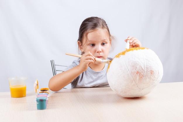 A criança faz artesanato para o halloween com entusiasmo, decoração de abóbora em papel machê, desenho com guache.