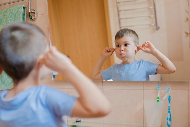A criança faz careta diante do espelho no banheiro.