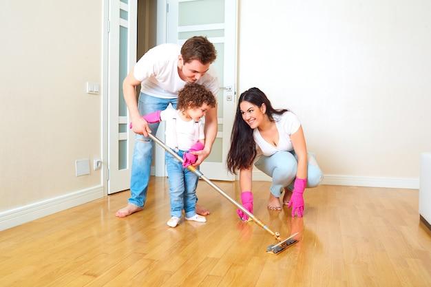 A criança faz limpeza úmida com mamãe e papai crianças na família criança limpa o chão no quarto com os pais o conceito de família e educação dos filhos