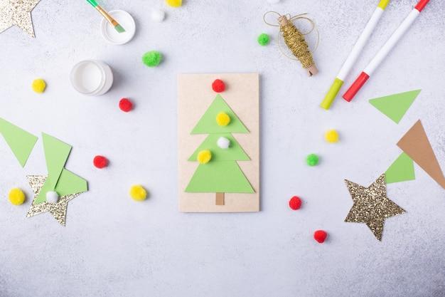 A criança faz um cartão de felicitações colagem de papel de natal, projeto de arte infantil, para crianças foto de alta qualidade
