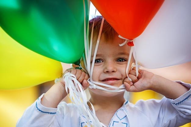 A criança feliz do retrato do close up com brinquedo colorido balloons no dia ensolarado do verão.