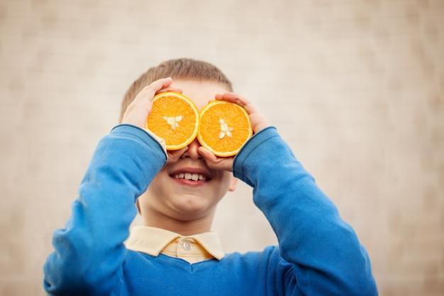 A criança feliz do retrato que guarda a laranja antes de seus olhos gosta no dia ensolarado.