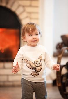 A criança feliz menina de pé em casa contra a lareira