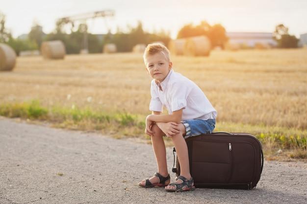 A criança feliz senta-se em uma mala no dia ensolarado de verão, o viajante