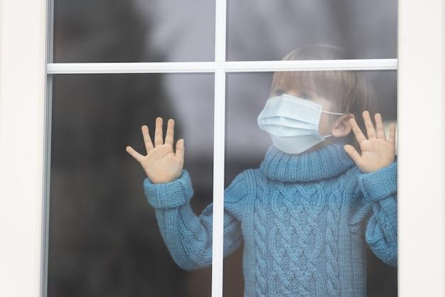 A criança fica em casa. criança com máscara de proteção.