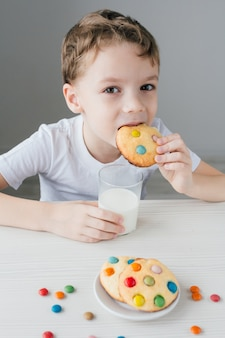 A criança fica feliz em comer biscoitos caseiros com leite