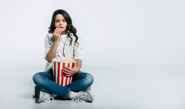 A criança focada está sentada em posição de lótus e comendo pipoca, enquanto assiste a desenhos animados ou filmes.
