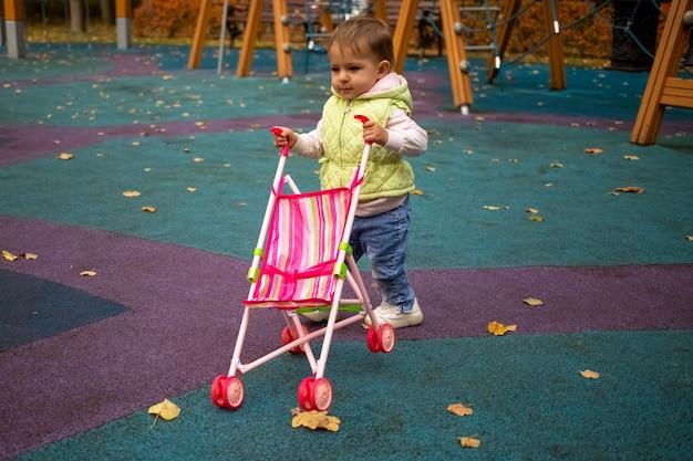A criança fofa carrega um carrinho de bebê para passear no parque de outono