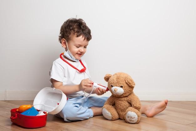 A criança interpreta um médico e injeta um ursinho de pelúcia. ensinando um remédio infantil através do jogo. escolha de profissão. vacinação.