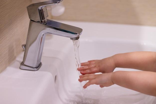 A criança lava as mãos. a menina lava as mãos com sabão debaixo de uma torneira com água corrente. fechar-se. conceito de higiene, limpeza e saúde