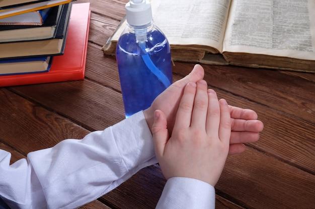 A criança lava as mãos com gel à mesa
