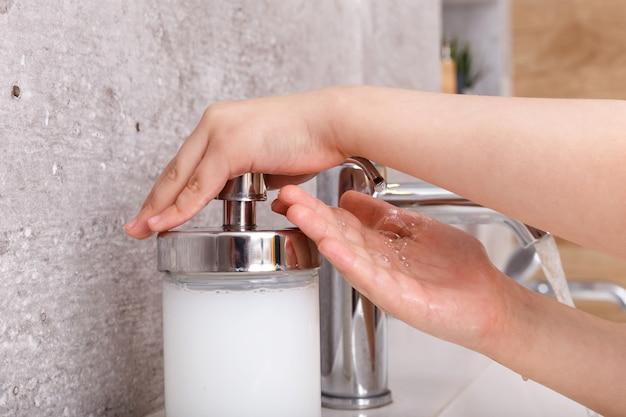 A criança lava as mãos com sabão.