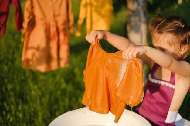 A criança lava roupas ao ar livre e as pendura para secar em um varal