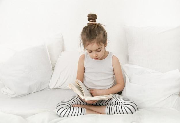 A criança lê um livro de pijama na cama. desenvolvimento infantil e conceito de aprendizagem.