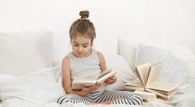 A criança lê um livro de pijama na cama. desenvolvimento infantil e espaço da cópia do conceito de aprendizagem.