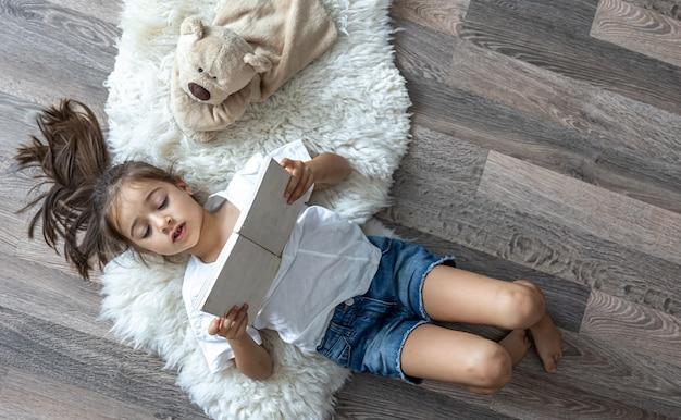 A criança lê um livro deitado sobre um tapete aconchegante em casa com seu ursinho de pelúcia de brinquedo favorito.