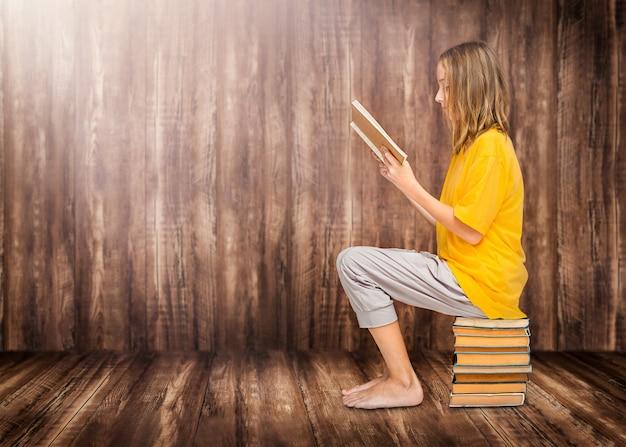 A criança lê um livro didático e se senta em uma pilha de livros sobre um fundo de madeira
