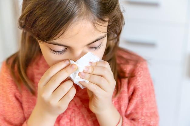 A criança limpa o nariz escorrendo com um guardanapo. foco seletivo. pessoas.