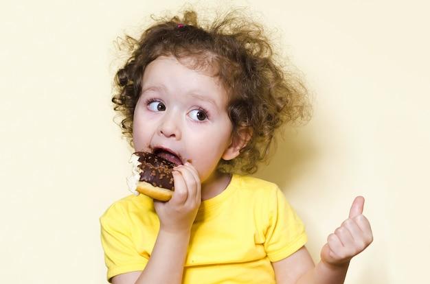 A criança manhosa prova a doçura. garota com ganância e apetite come, morde deliciosa rosquinha de chocolate e levanta um dedo na tendência de parede amarelo. emoções humanas em alimentos